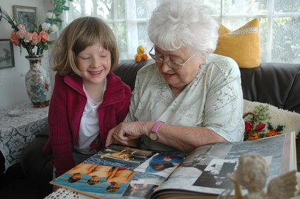 grandmother grand daughter looking at family pictures